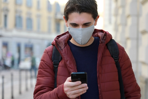 保護マスクを持った男が通りを歩いている間彼のスマートフォンを見る