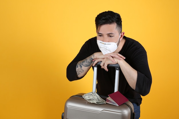 Man with protective mask suitcase and passport, listening to music,