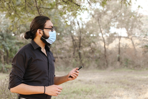 Man with a protective mask using a mobile in nature