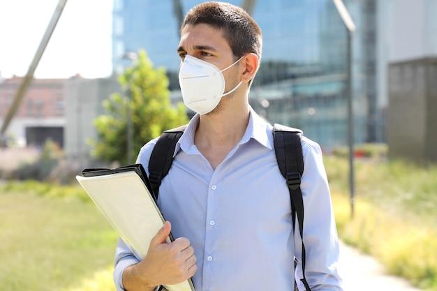 街の通りを歩いている保護マスクを持つ男