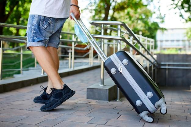 保護マスクを持った男、スーツケースを持って通りを歩く、コロナウイルスのパンデミック中の生活、空の旅、旅行のコンセプト。