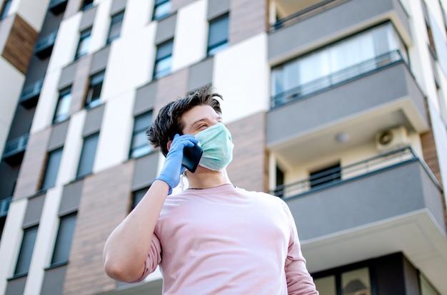 Человек с защитной медицинской одежды с помощью мобильного телефона, прогулка по улице города street.guy носить защитную маску и перчатки на улице