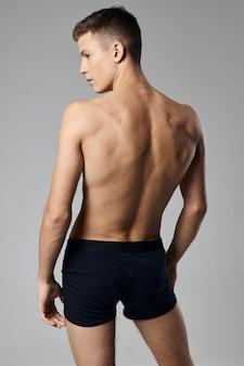 腕の筋肉をポンプでくみ上げた男裸の背中灰色の背景モデル