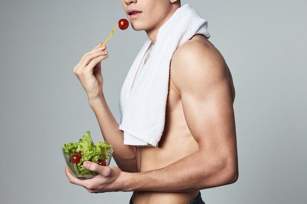 サラダ健康食品と肩のプレートにポンプでくみ上げられたボディタオルを持つ男