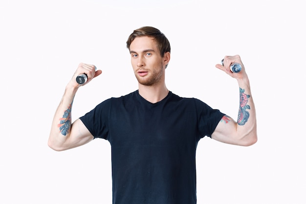 Man with pumped up muscles of arms and dumbbells black tshirt white background