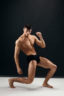 Мужчина с накачанным мускулистым телом в черных трусиках позирует на темном студийном фоне