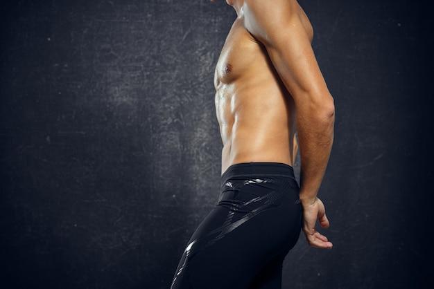 ポンプアップされた筋肉の体のトレーニングエクササイズジム暗い背景を持つ男