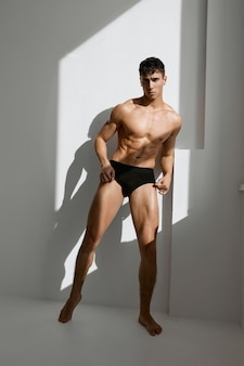 Man with pumped up naked body black panties near the window