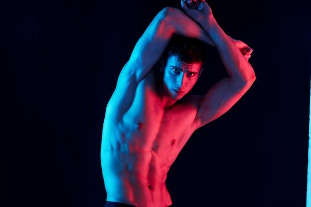 어두운 배경에 몸짓으로 펌핑된 팔 근육을 가진 남자