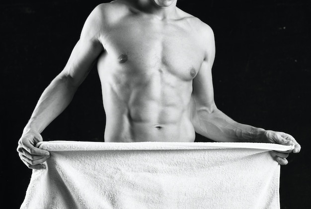 A man with a pumpedup body covers himself with a towel studio fitness