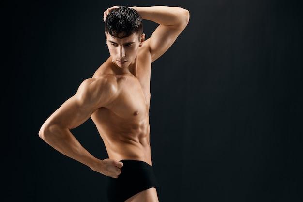 Man with a pumpedup torso athlete dark background studio