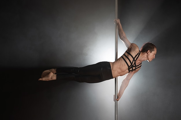 Man with pylon male pole dancer dancing on a black background