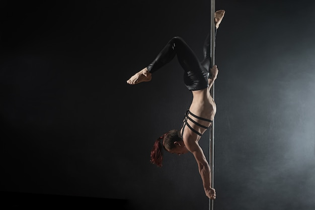 Man with pylon, male pole dancer dancing on a black background