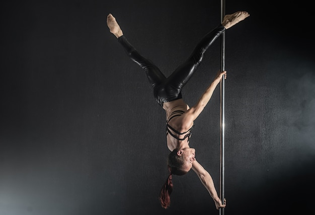 Man with pylon. male pole dancer dancing on a black background