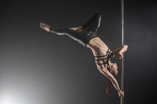 Man with pylon. male pole dancer dancing on black
