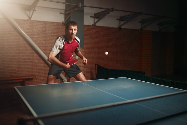 Man with racket in action, playing table tennis. ping pong training, high concentration sport