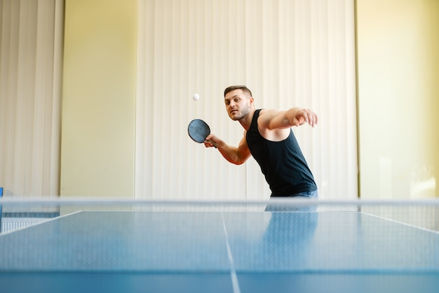 Man with racket and ball playing ping pong indoors.