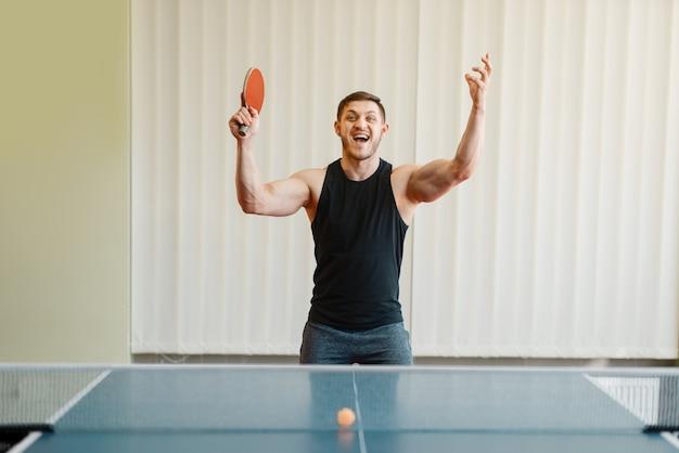 Человек с ракеткой в руке выигрывает турнир по настольному теннису в помещении.