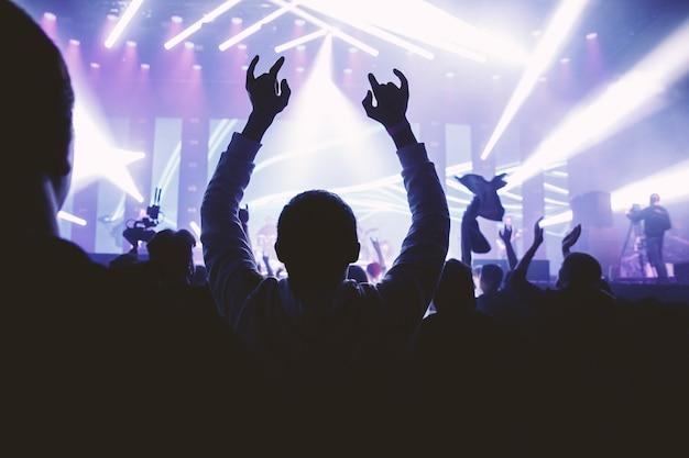 제기 손으로 남자는 음악 쇼를 즐깁니다. 콘서트에 행복 군중
