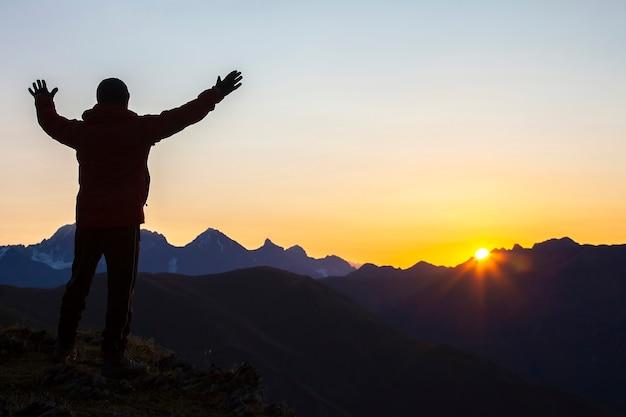 일출에 산 얼굴에 서 제기 손으로 남자. 산의 관광 여행자가 맑은 새벽을 만나다