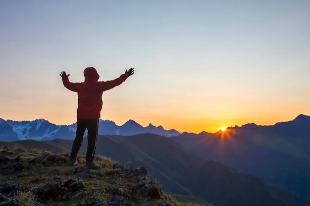 일출에 산 얼굴에 서 제기 손으로 남자. 산의 관광 여행자가 맑은 새벽을 만난다.