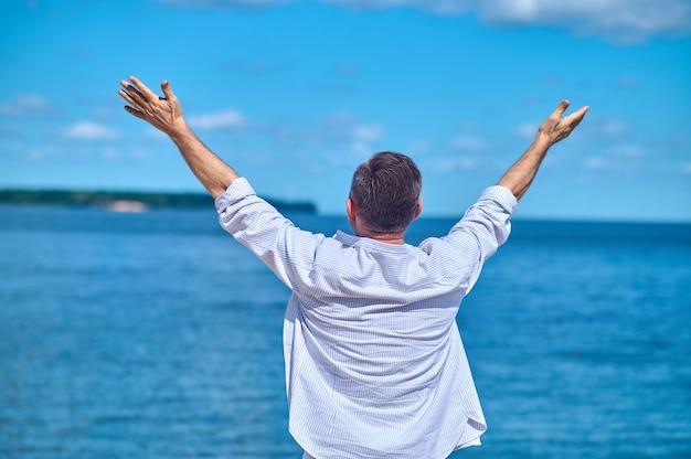 Человек с поднятыми руками спиной к камере