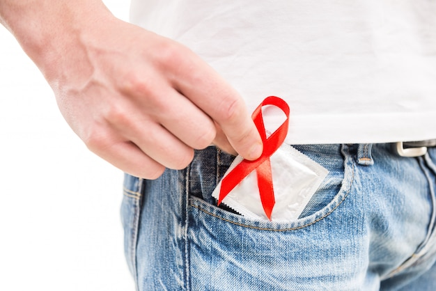 Man with red aids awareness ribbon with condom in hand.