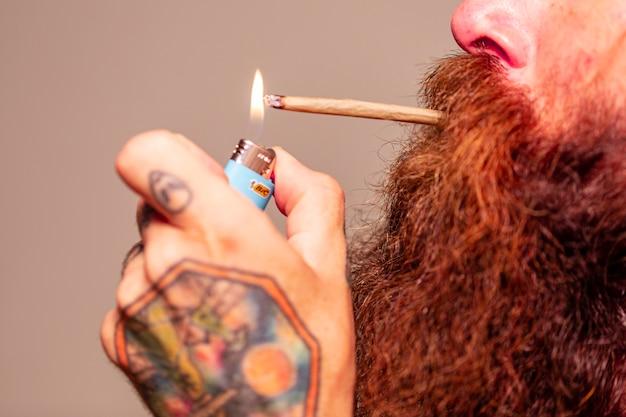 Человек с рыжей бородой курит косяк.
