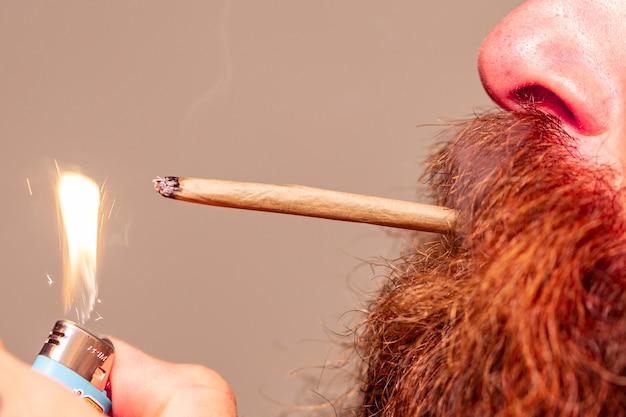 Мужчина с рыжей бородой курит косяк.