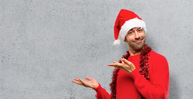 Man with red clothes celebrating the christmas holidays extending hands to the side