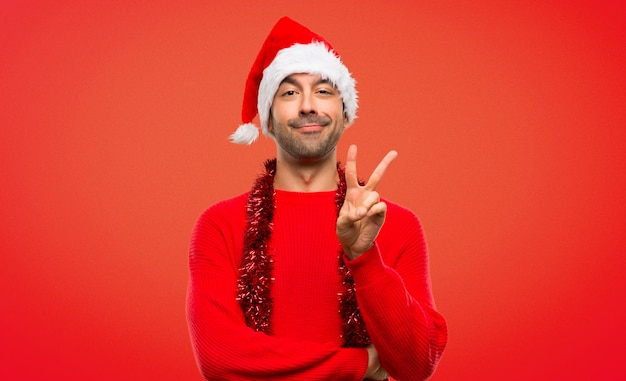 Man with red clothes celebrating the christmas holidays happy and counting two