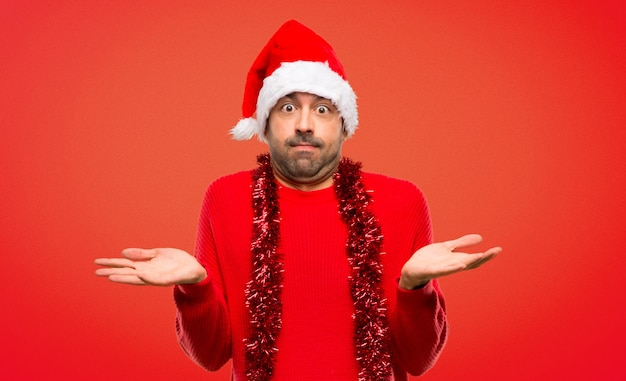 Man with red clothes celebrating the christmas holidays having doubts while raising hands