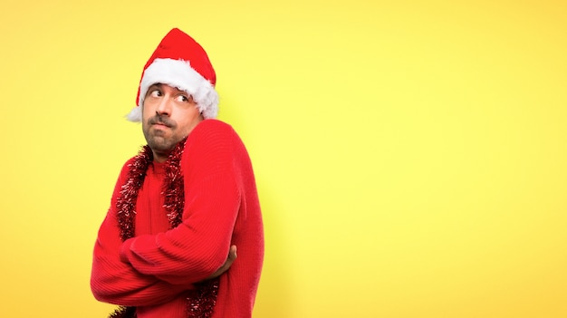 Man with red clothes celebrating the christmas holidays making doubts gesture