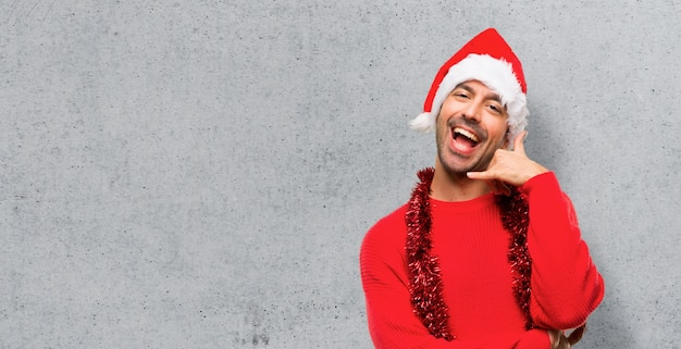 Man with red clothes celebrating the christmas holidays making phone gesture.