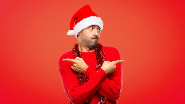 Man with red clothes celebrating the christmas holidays pointing to the laterals having do