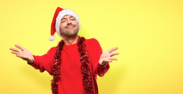 Man with red clothes celebrating the christmas holidays presenting and inviting to come