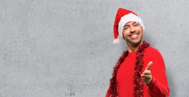 Man with red clothes celebrating the christmas holidays shaking hands for closing a good d
