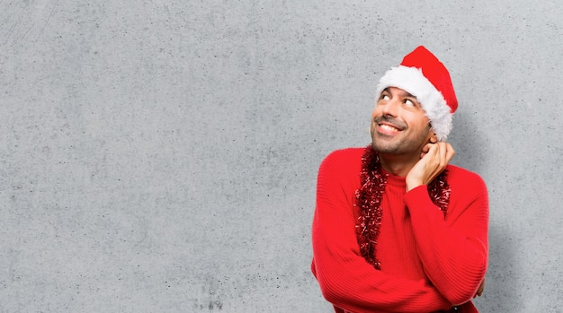 Man with red clothes celebrating the christmas holidays standing and thinking an idea
