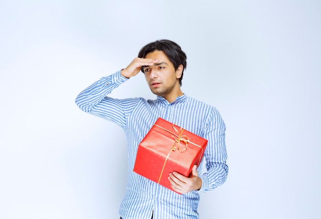 Man with a red gift box looks tired and bored. high quality photo