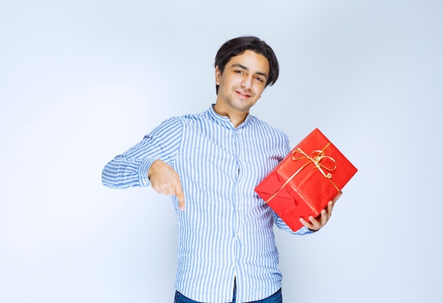 Man with a red gift box noticing a person ahead and calling him to present the gift. high quality photo