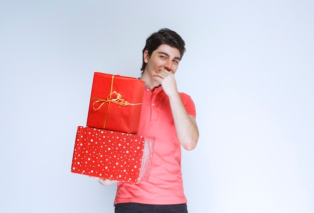 彼の口に手を置いて考えている赤いギフトボックスを持つ男。