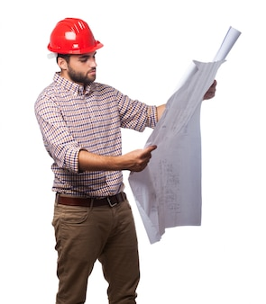 Man with a red helmet and looking blueprints