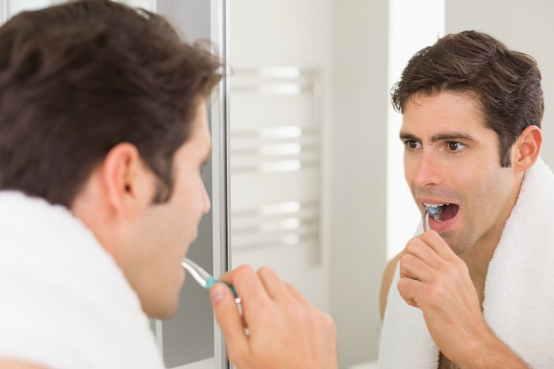 Man with reflection brushing teeth in the bathroom