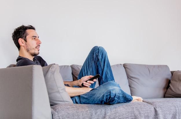 テレビを見ているソファのリモコンを持つ男。本当の率直なイメージ