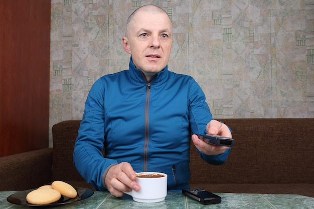 Man with the remote for the tv in hand, drinking coffee
