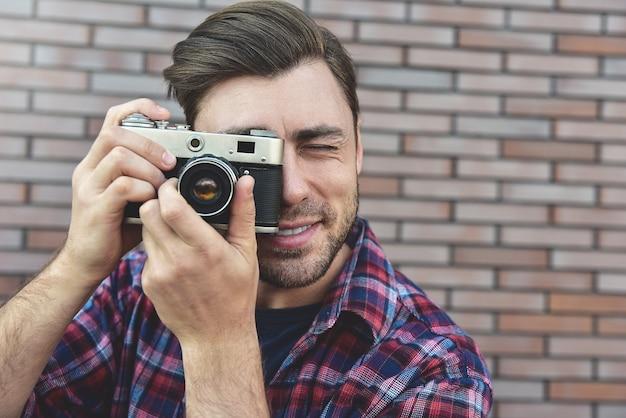 レンガの壁の表面に立っている間、レトロな写真カメラファッション旅行ライフスタイル屋外の男