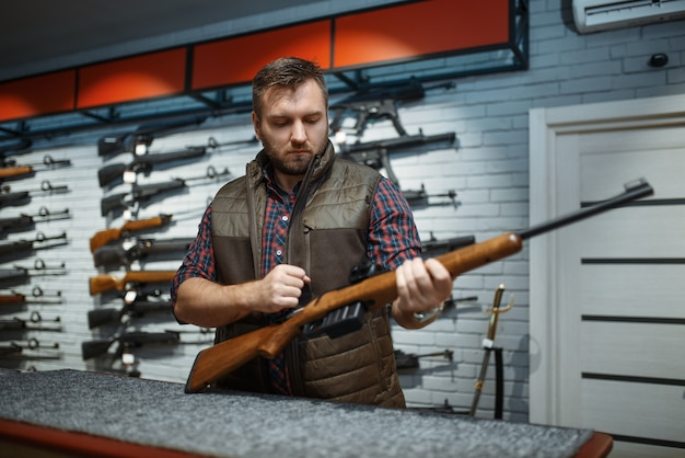 Man with rifle standing at counter in gun shop. euqipment for hunters on stand in weapon store, hunting and sport shooting hobby