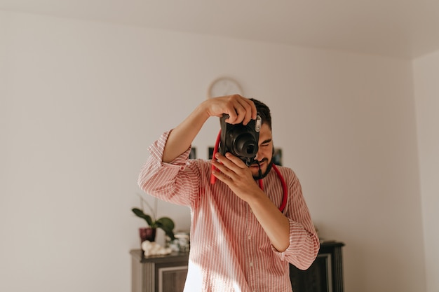 L'uomo con l'anello al dito fa la foto sulla fotocamera. istantanea del ragazzo brunet in abito a righe in un appartamento spazioso.