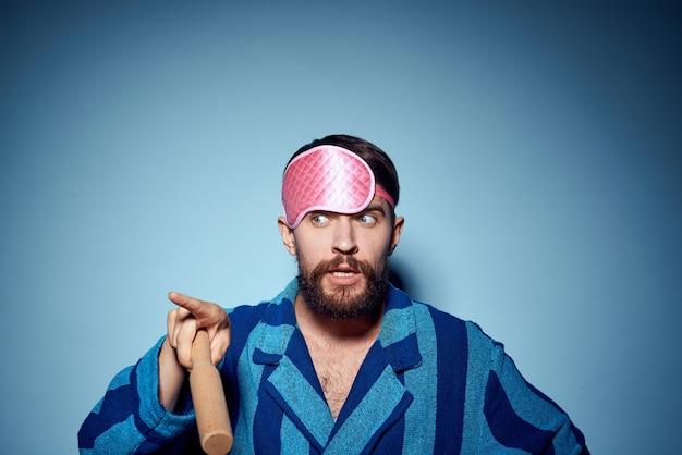 Человек со скалкой и в розовой маске для сна в синем халате обрезанный вид модели эмоции
