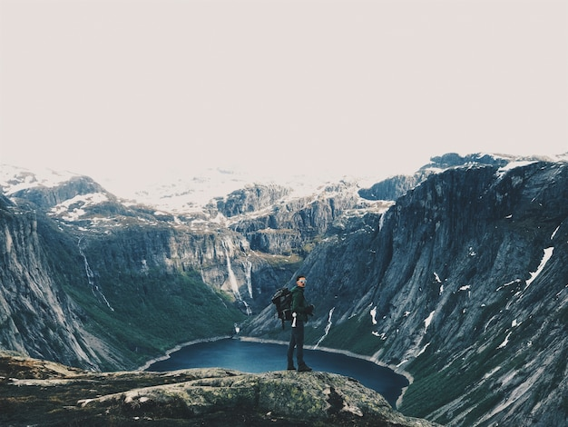 Man with a rucksack admires gorgeous mountain landscape